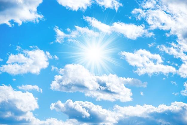 Sonne mit sonnenstrahlen und wolken am blauen himmel als naturhintergrund