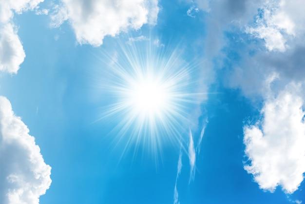 Sonne mit strahlen und weißen wolken am strahlend blauen himmel