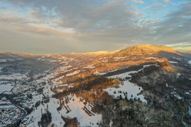Sonne scheint auf schneebedeckten bergen über dorf und straße im winterabend.