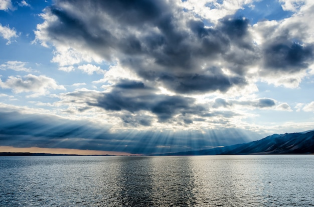 Sonne scheint durch dichten bewölkten himmel, silberstreifen