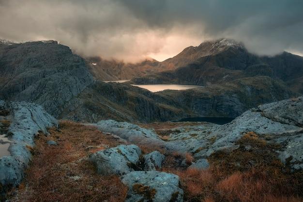 Sonne scheint durch regenwolken über einem see in den norwegischen bergen auf den lofoten
