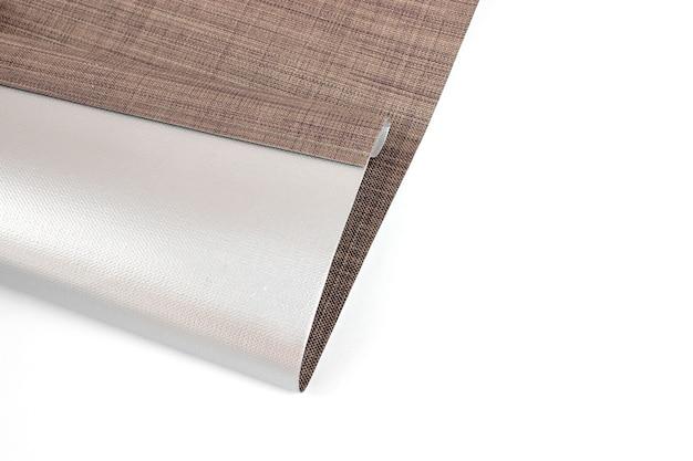 Sonnen- und hitzeschutz. rollos werden aus texturmaterial hergestellt. nahaufnahme von raffrollos oder rollos aus leinenstoff.