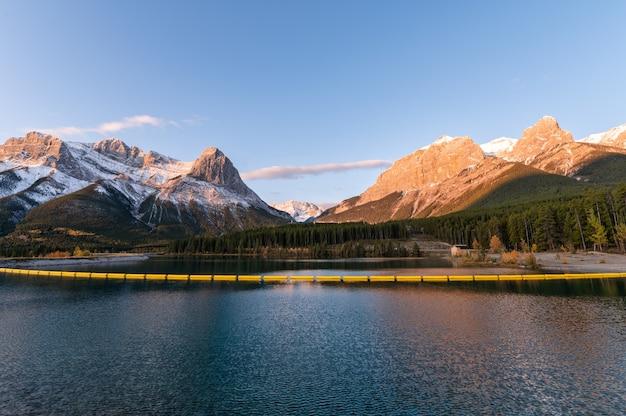 Sonnenaufgang auf rocky mountains mit blauem himmel auf rundle forebay reservoir
