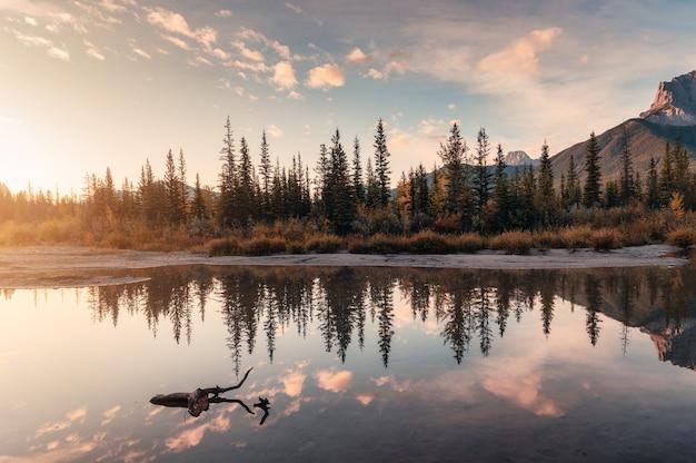 Sonnenaufgang auf rocky mountains und herbstwaldreflexion auf dem fluss im nationalpark. canmore, alberta, kanada