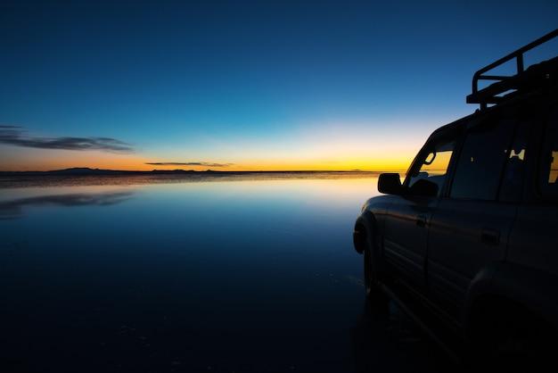 Sonnenaufgang auf salar de uyuni in bolivien bedeckt mit wasser, auto in der salzwüste und himmelsreflexionen
