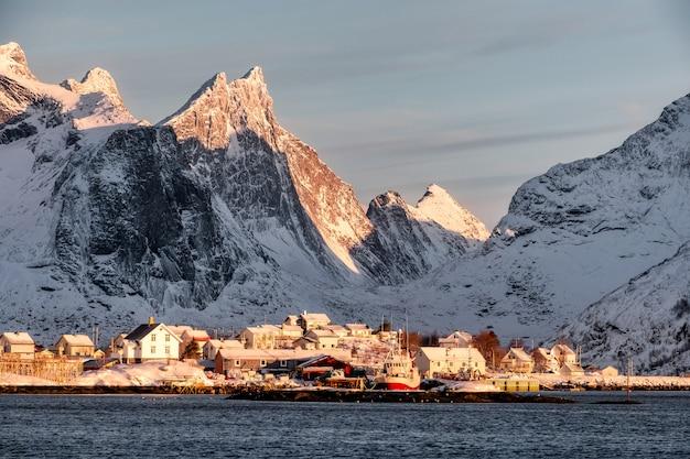 Sonnenaufgang auf skandinavischem dorf mit schneegebirgshintergrund auf küstenlinie