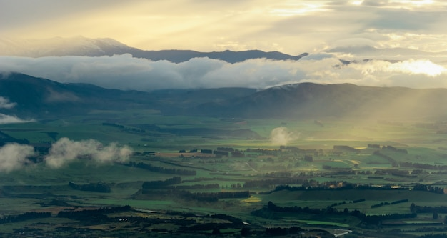 Sonnenaufgang lichtstrahlen treffen auf die grüne tallandschaft kepler track neuseeland