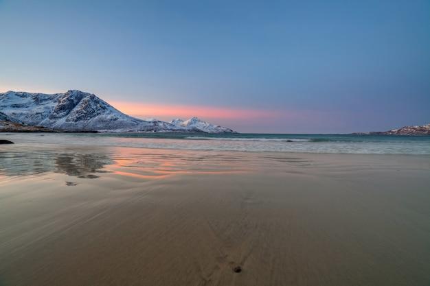 Sonnenaufgang mit erstaunlicher magentafarbener farbe über sandstrand und fjord. tromso, norwegen. winter. polare nacht. lange verschlusszeit