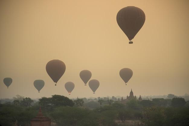 Sonnenaufgang mit staubigem rauch und vielen heißluftballonen über der bagan archäologischen zone in
