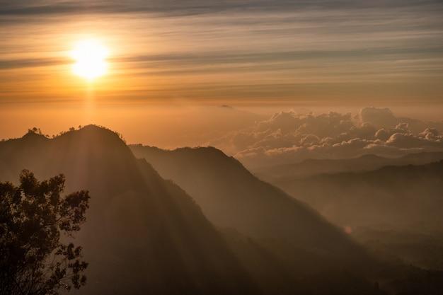 Sonnenaufgang über berg mit nebel mit dorf auf hügel