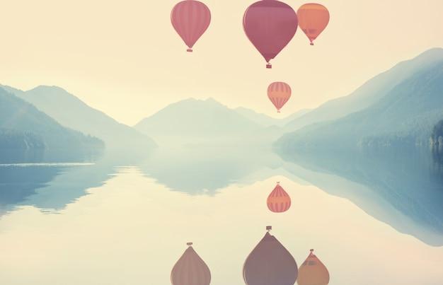Sonnenaufgang über dem bergsee mit luftballons oben. reise-hintergrund.