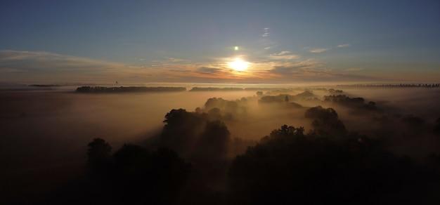 Sonnenaufgang über dem nebel im tal in der nähe des dorfes.