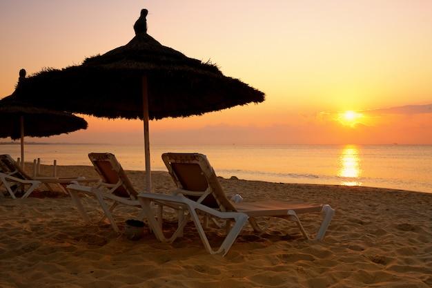 Sonnenaufgang über dem sonnenschirm am strand, tunesien