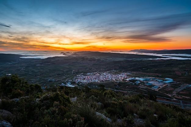 Sonnenaufgang über einem tal zwischen bergen mit nebel la font de la figuera valencia spain