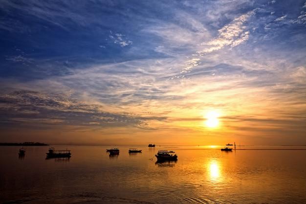 Sonnenaufgang über fischerbooten auf bali