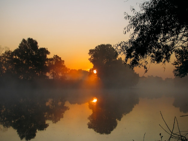 Sonnenaufgang und nebel am fluss