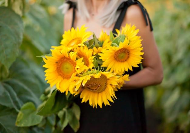 Sonnenblume in den händen der frau auf sonnenblumenfeld.