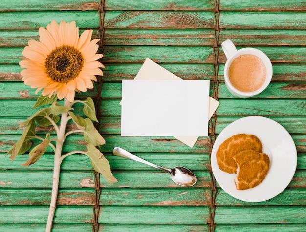 Sonnenblume; löffel; leere karten; gegessene plätzchen und kaffeetasse auf grünem hölzernem hintergrund