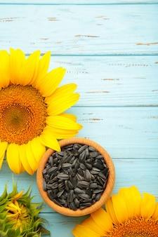 Sonnenblume mit samen in schüssel auf blauem hintergrund aus holz. ansicht von oben