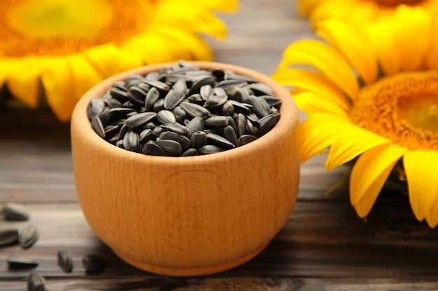 Sonnenblume mit samen in schüssel auf braunem holzuntergrund