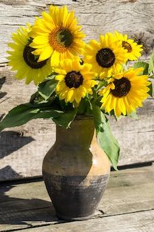 Sonnenblumen im vintage tonkrug auf holzuntergrund