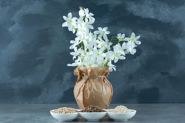 Sonnenblumen, kürbiskerne und reiskörner in weißen tassen. foto in hoher qualität