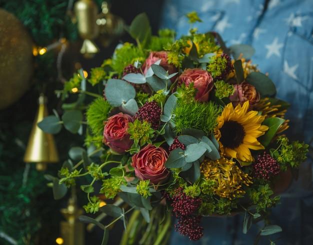 Sonnenblumen- und rosenblumenstrauß im weihnachtshintergrund bild