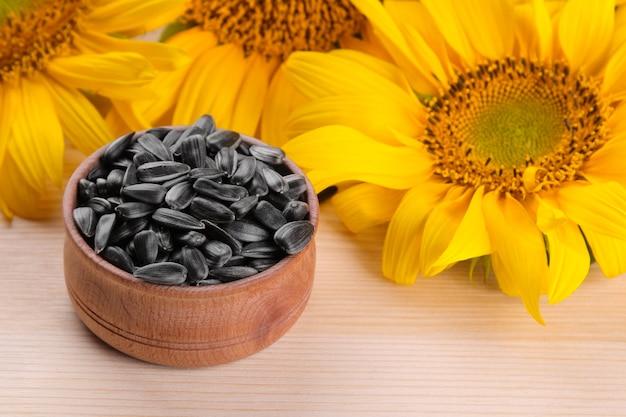Sonnenblumenkerne in einer holzschale und mehrere schöne gelbe sonnenblumen auf einem natürlichen holzhintergrund