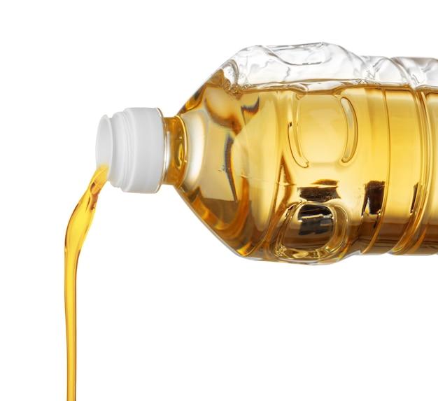 Sonnenblumenöl, das von der flasche lokalisiert auf weißem hintergrund gießt