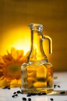 Sonnenblumenöl im transparenten krug mit sonnenblumenblüten