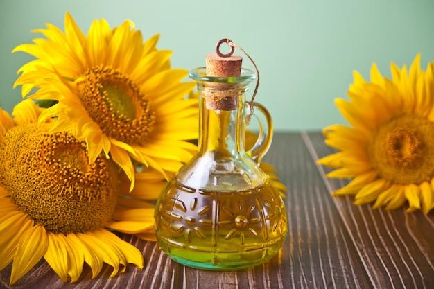 Sonnenblumenöl in einer flasche auf dem holztisch.