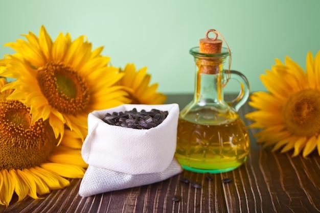 Sonnenblumenöl in einer flasche und sonnenblumenkerne auf dem holztisch.