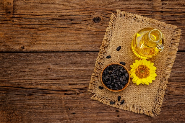 Sonnenblumenöl in glasschale mit blume und samen