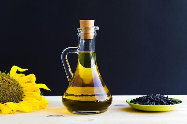 Sonnenblumenöl mit blume und samen in einem glaskrug.