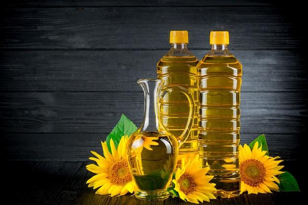 Sonnenblumenöl mit blumen auf schwarzem rustikalem hintergrund