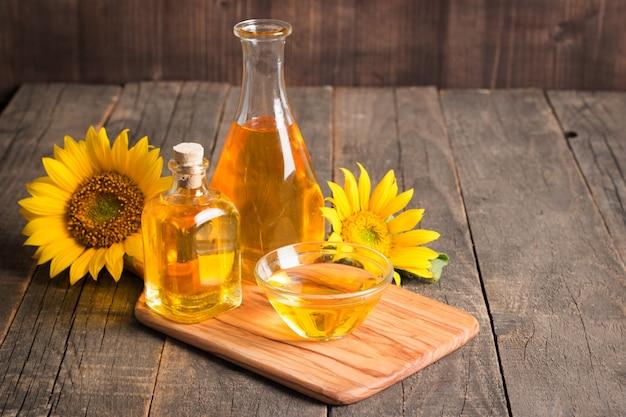 Sonnenblumenöl mit samen auf traditionellem rustikalem holz