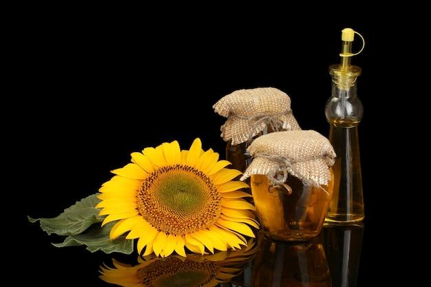 Sonnenblumenöl und sonnenblumen isoliert auf schwarz
