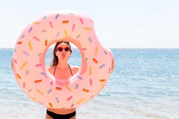 Sonnenbräune genießen. schöne verrückte frau, die sich mit aufblasbarem ring im meeresstrand entspannt und spielt. sommerferien und urlaubskonzept.