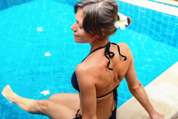 Sonnenbräunende frau in der nähe mit einem schwimmbad