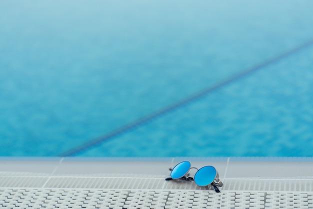 Sonnenbrille am blauen pool