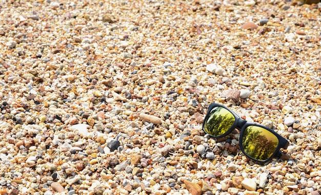 Sonnenbrille auf dem kieselstrandhintergrund. sommertagskonzept ferien- und ferienkonzept.