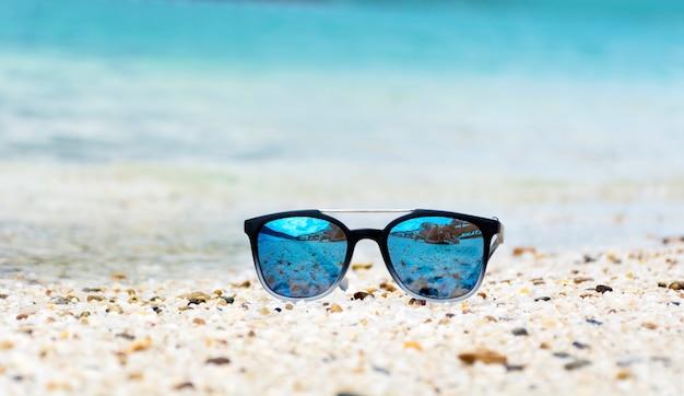 Sonnenbrille auf dem sand
