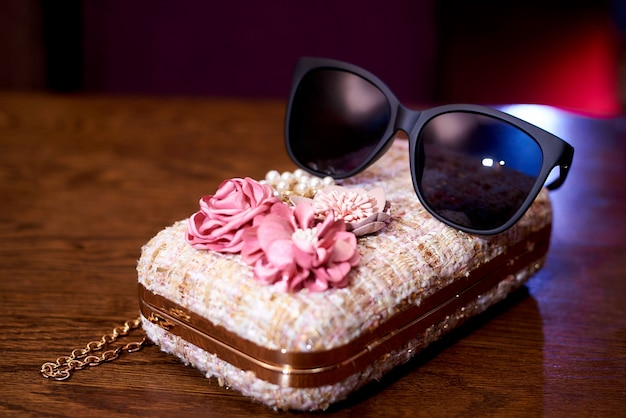Sonnenbrille auf einer stilvollen handtasche der kleinen frauen.