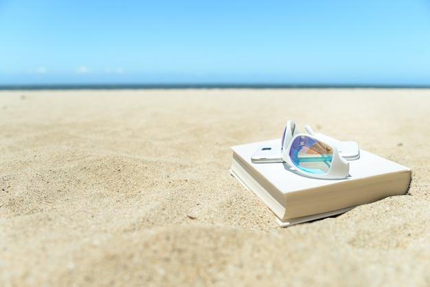 Sonnenbrille, buch und telefon am strand