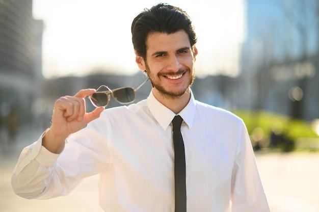 Sonnenbrille des jungen geschäftsmanns im freien haltend