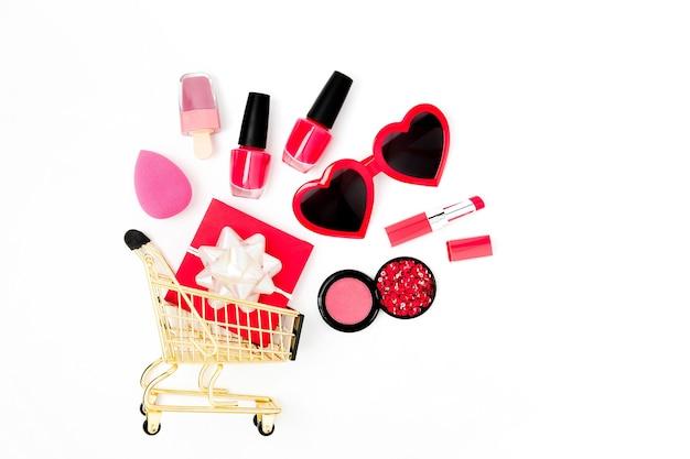 Sonnenbrille, geschenk und kosmetik in einem warenkorb auf weißem hintergrund. valentinstag einkaufen. flache lage, ansicht von oben