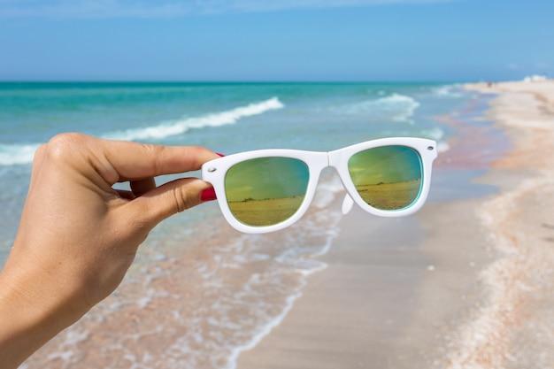 Sonnenbrille in der hand am strand