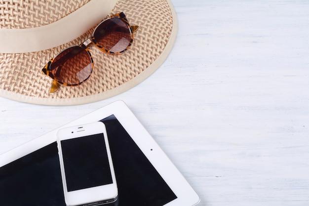 Sonnenbrille mit einem hut, einem digitalen tablet und einem smartphone.