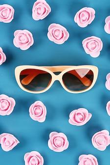 Sonnenbrille mit kleinen rosen auf blauem hintergrund. draufsicht. sommerhintergrund.