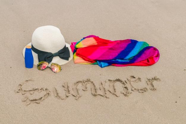 Sonnenbrille, sonnencreme und hut auf weißem sandstrand